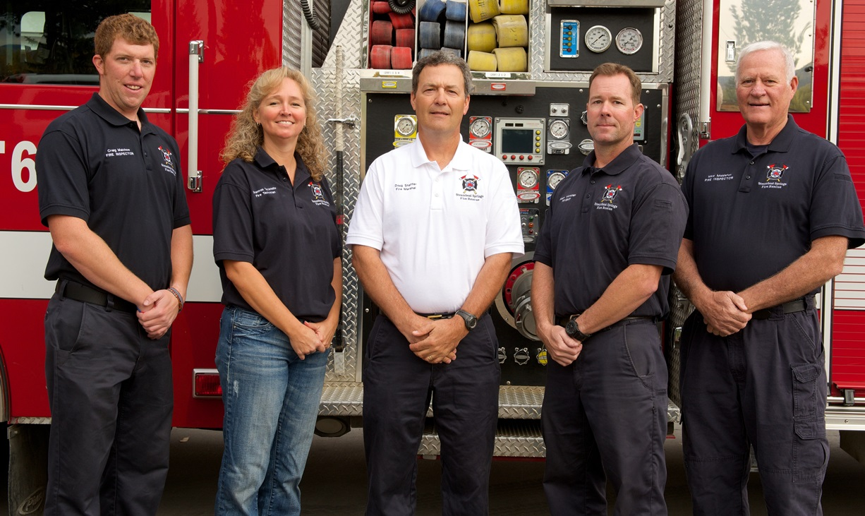Five members of Fire Prevention in front of red truck