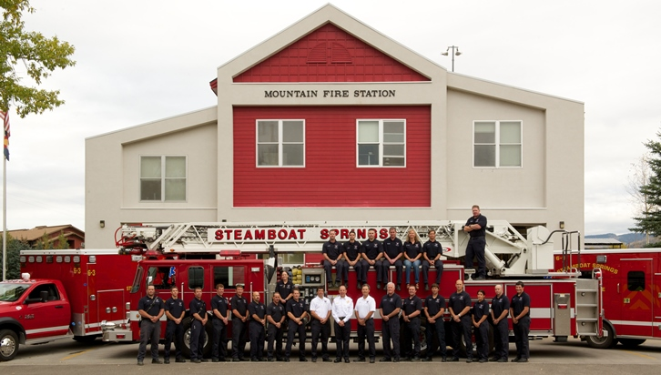 Image of Fire Department outside fire station in front of fire truck