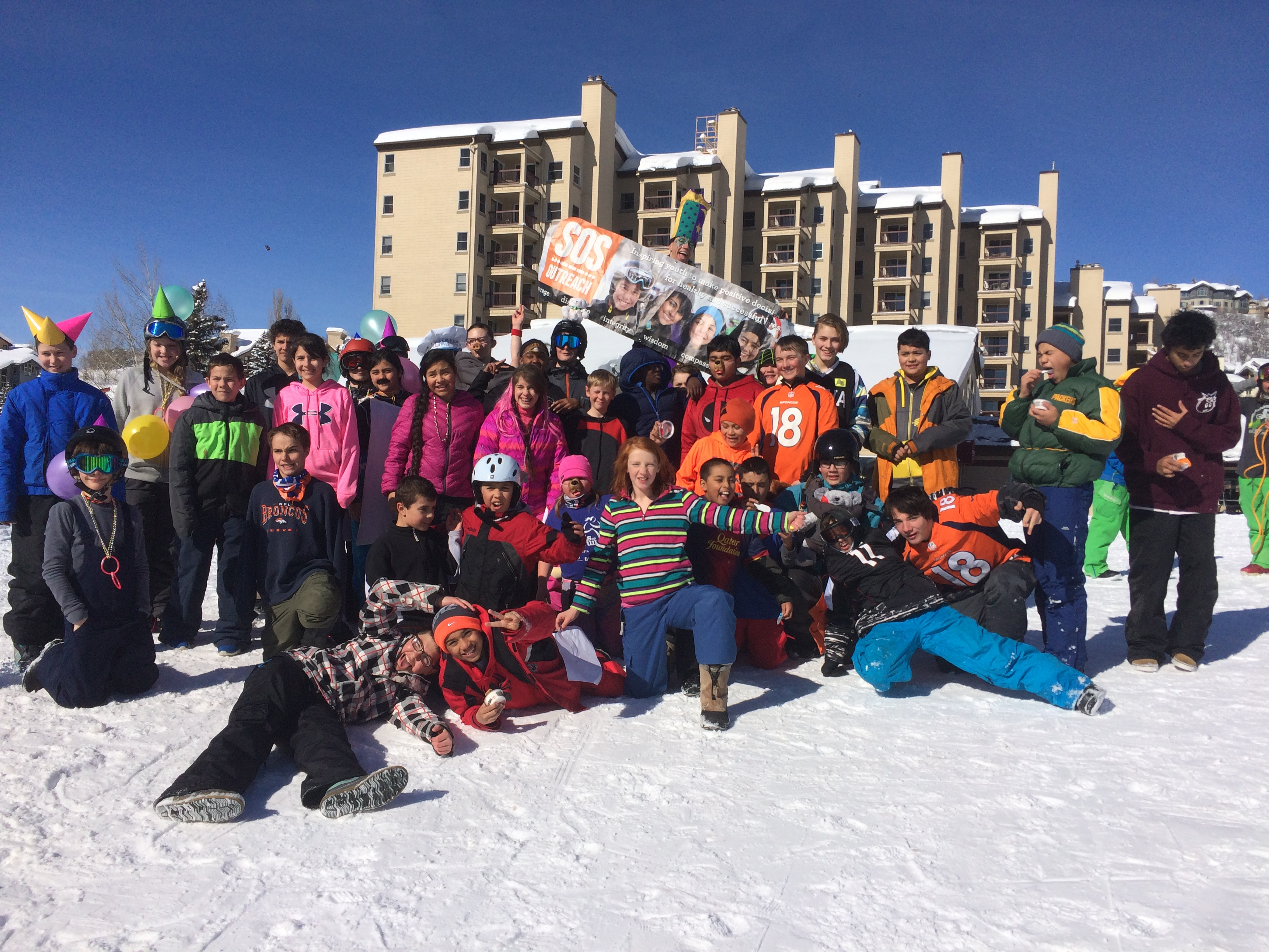Group photo of youth standing in snow in snowboarding gear