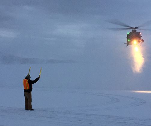 Crew landing Helicopter in snow